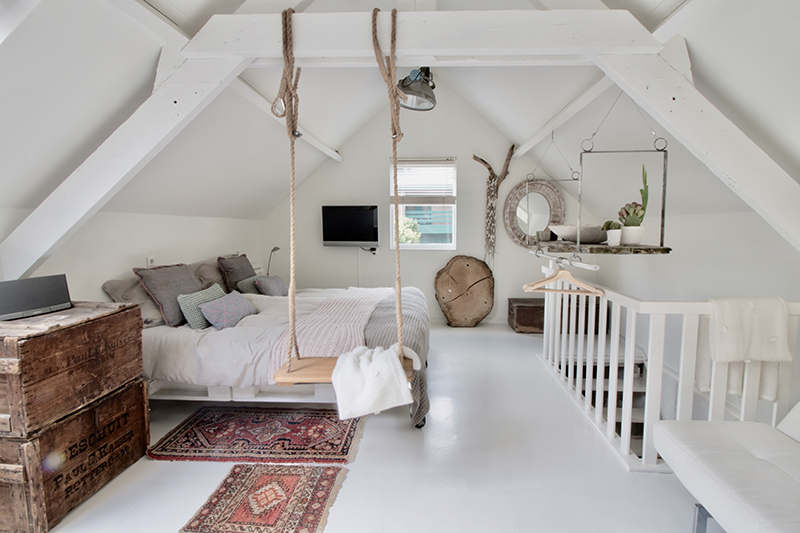 een opgeruimde zolder die is omgetoverd naar slaapkamer voor meer ruimte